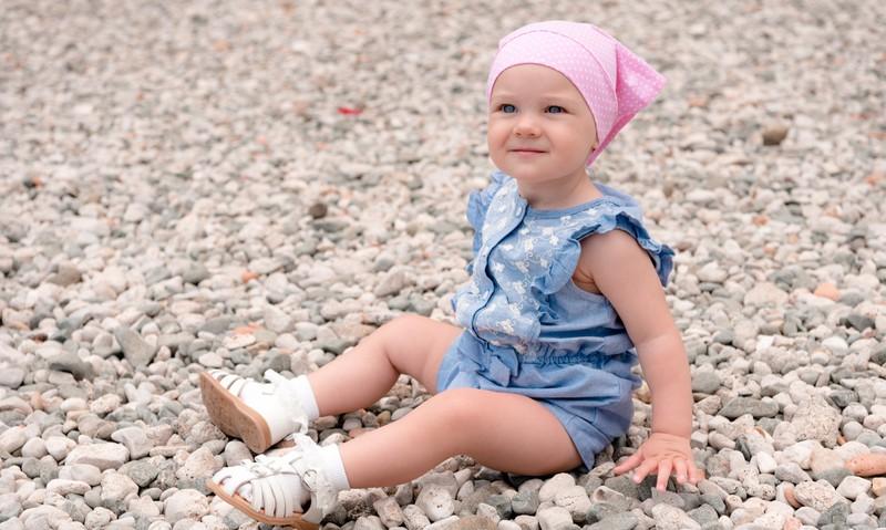 Ein kleines Mädchen sitzt auf Steinen