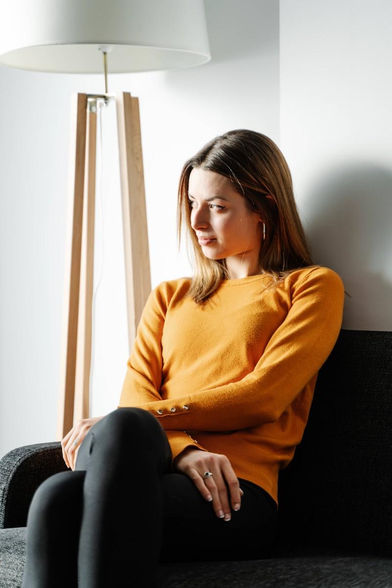 Eine Frau, die alleine auf einem Sofa sitzt und sich unbeobachtet fühlt