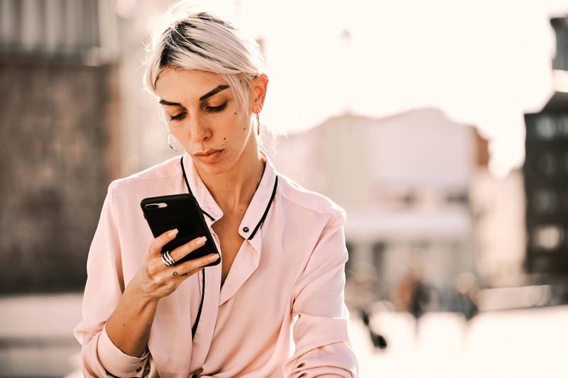 Eine Frau, die auf ihr Handy schaut, weil sie eine blöde Nachricht erhalten hat, die schlecht ankommt