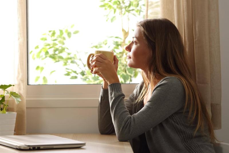 Eine Frau, die aus dem Fenster schaut und denkt, dass das Leben nicht fair ist