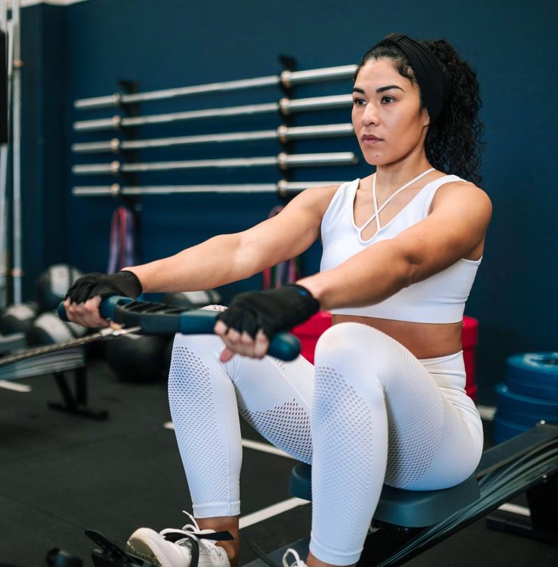 Frau rudert und macht ein Workout