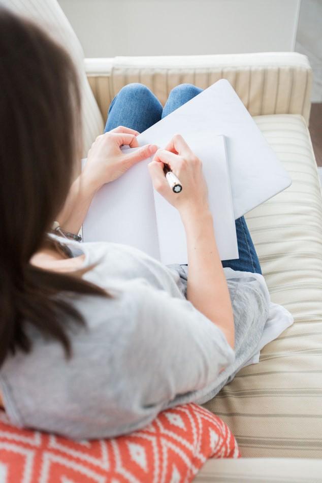 Frau, die auf dem Sofa liegt und schreibt