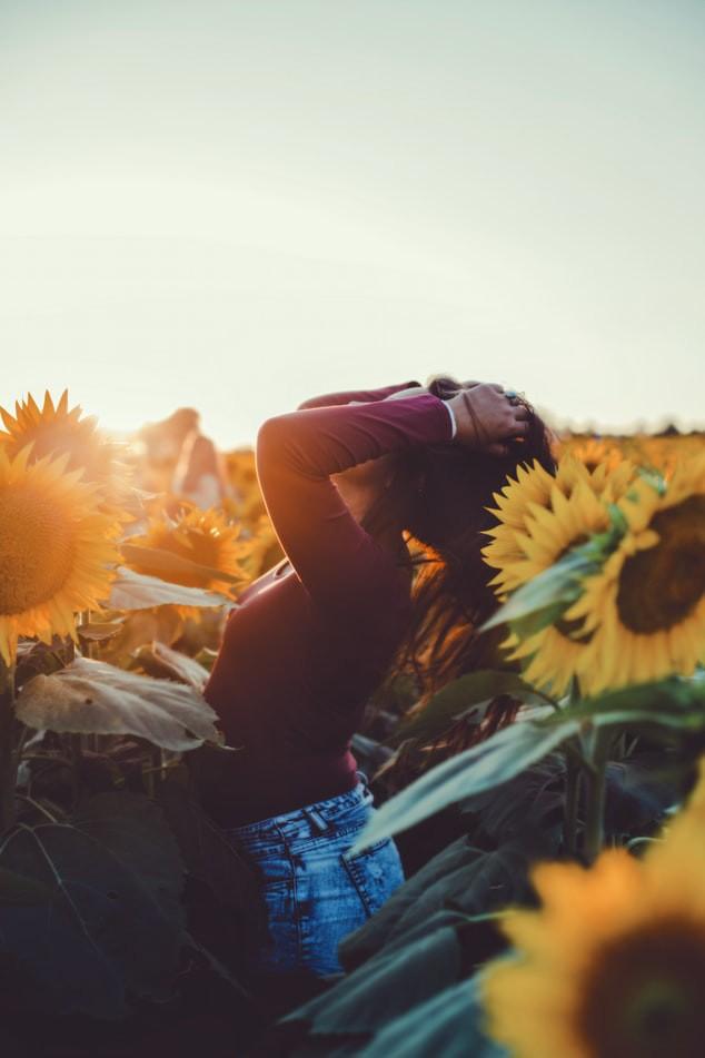 Frau, die im Spätsommer auf einem Feld voller Sonnenblumen steht