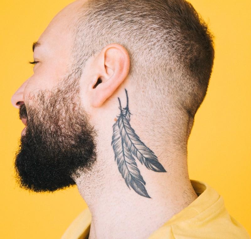Jemand mit einem Feder-Tattoo hinterm Ohr.