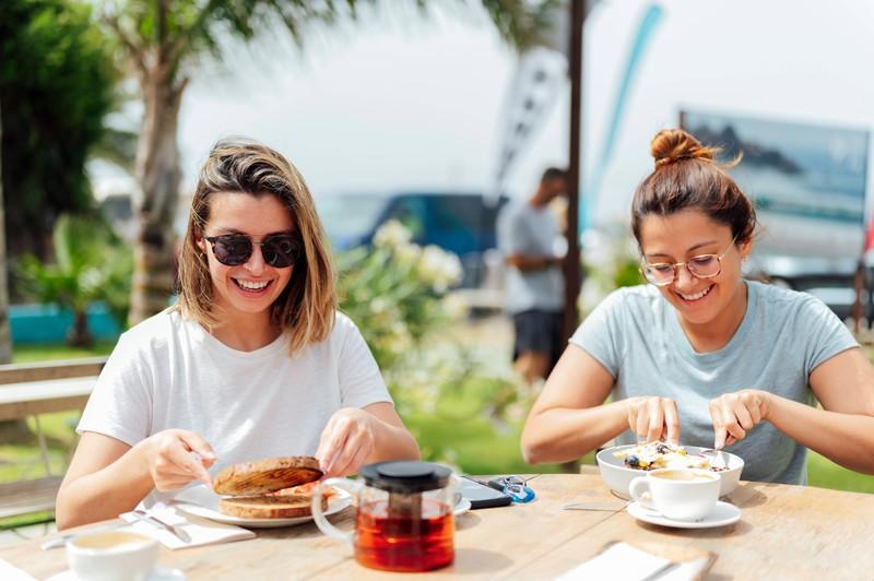 Die jungen Frauen schlagen beim Essen herzlich zu, weil sie sich in ihrem Körper wohlfühlen und keine Gedanken an Diäten verschwenden.