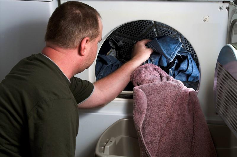 Ein Mann reinigt seine Jeans im Trockner.