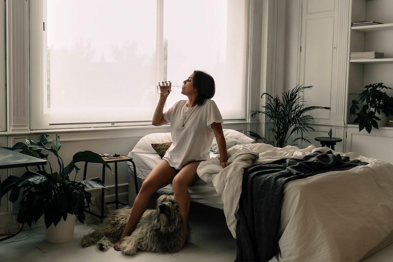 Man sieht eine Frau, die mit ihrem Hund im Zimmer geschlafen hat. Das kann Hitze hervorrufen