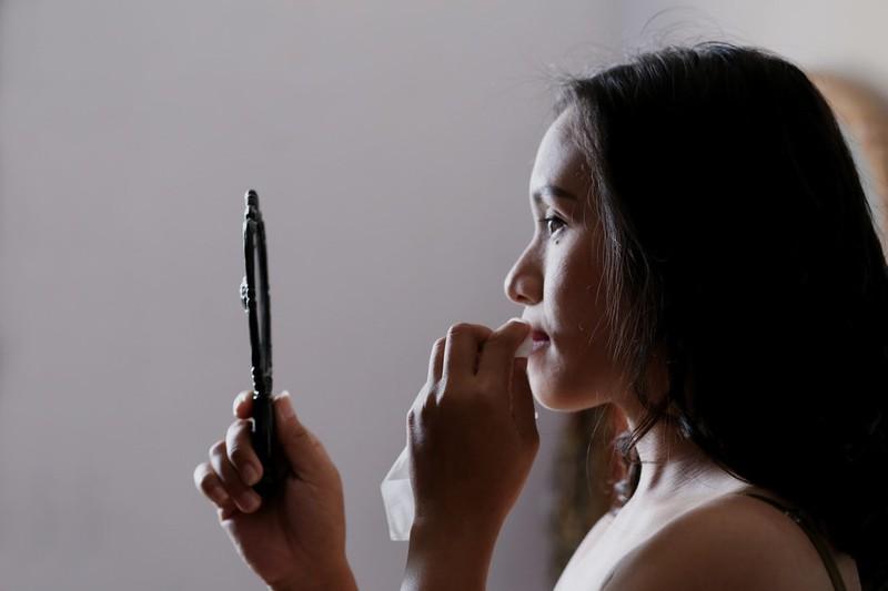 Dieses Bild zeigt eine Frau, die ihr Make-up mit den Händen auffrischt.