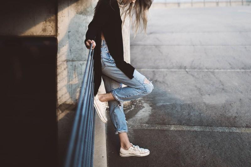 Die Frau trägt einen legere Jeans, um ihre dünnen Beine zu kaschieren.