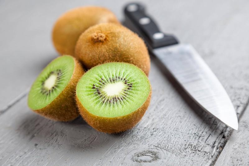 Man sieht eine Kiwi, welche ein Lebensmittel für eine reine Haut ist.