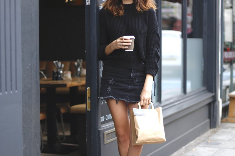 Eine dünne Frau, die einen Kaffee in der Hand hält und durch die Stadt schlendert