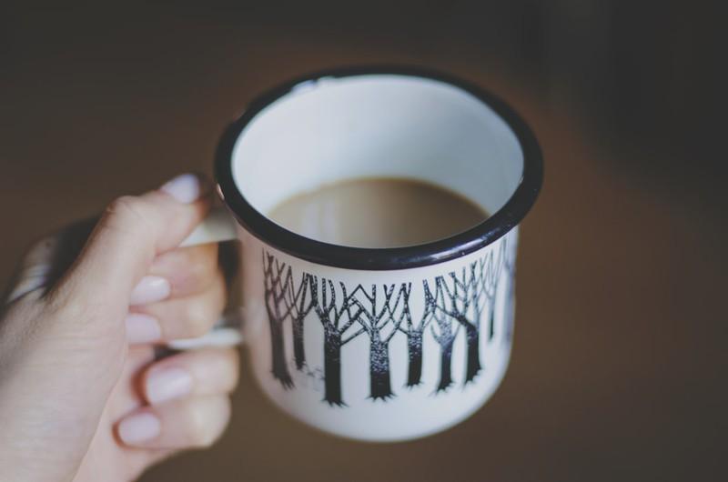 Frau, die eine Kaffeetasse in der Hand hält