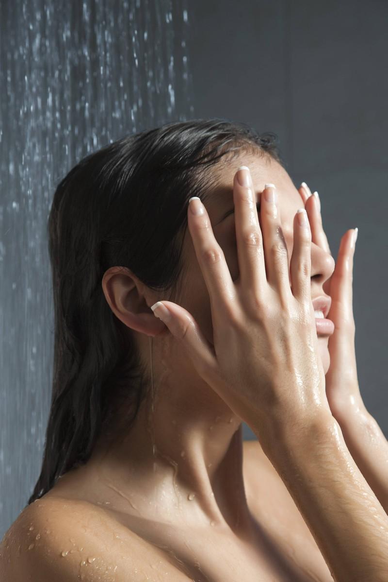 Man sieht eine Frau, die unter der Dusche steht und ihren Schweiß abwäscht