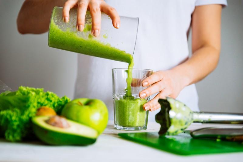 Frau gießt einen grünen Smoothie ein