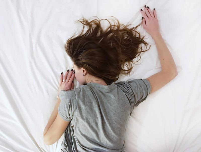 Frau, die mit offenem Haar im Bett liegt