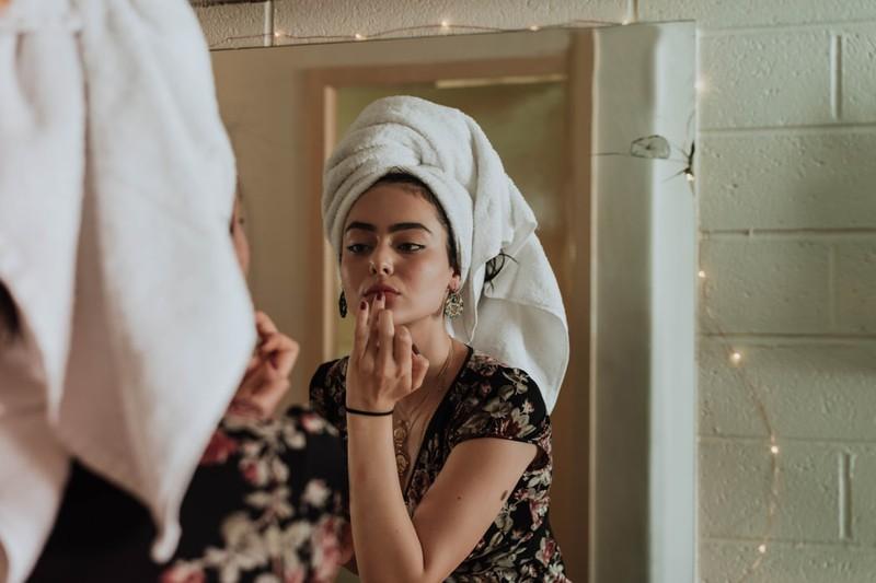 Frau mit Handtuchturban, um nasses Haar zu trocknen