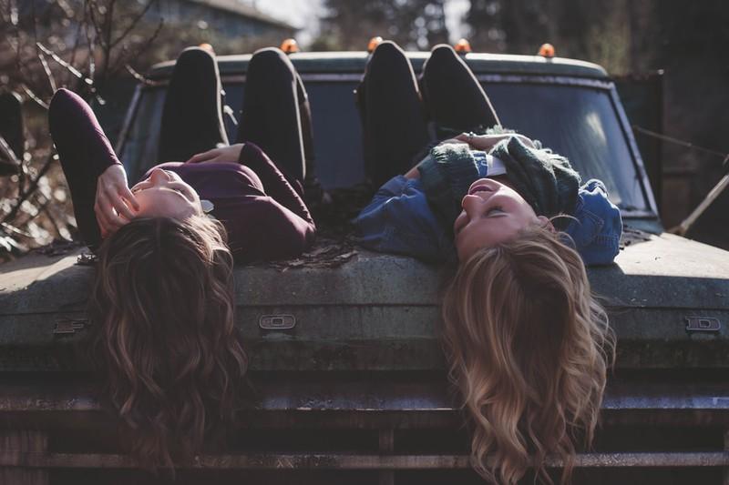 Zwei Frauen mit langen Haaren, die auf einem Auto liegen