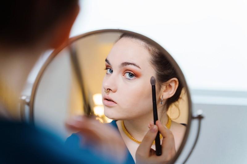 Frau betont ihre Augen mit Lidschatten, um von ihrem platten Haar abzulenken.