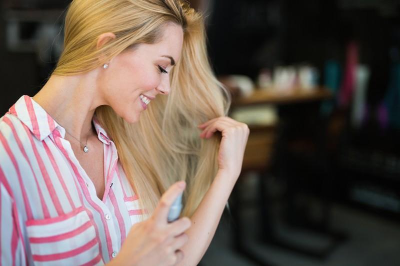 Frau nutzt Trockenshampoo für mehr Volumen im Haar.