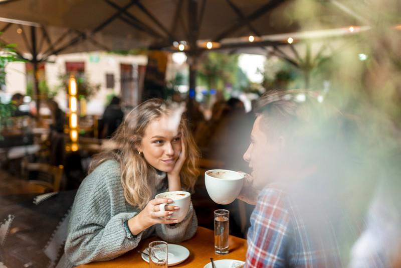 Frau hält Kaffeetasse und schaut Mann in die Augen