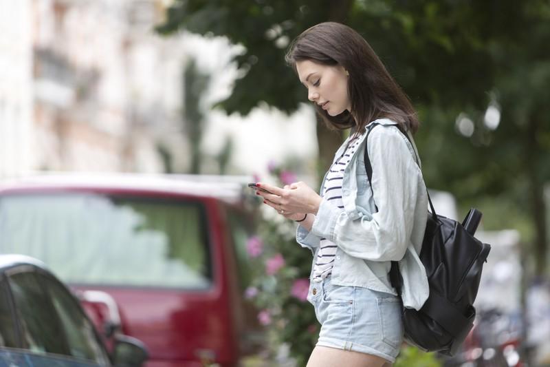 Junge Frau schreibt Nachricht auf Smartphone