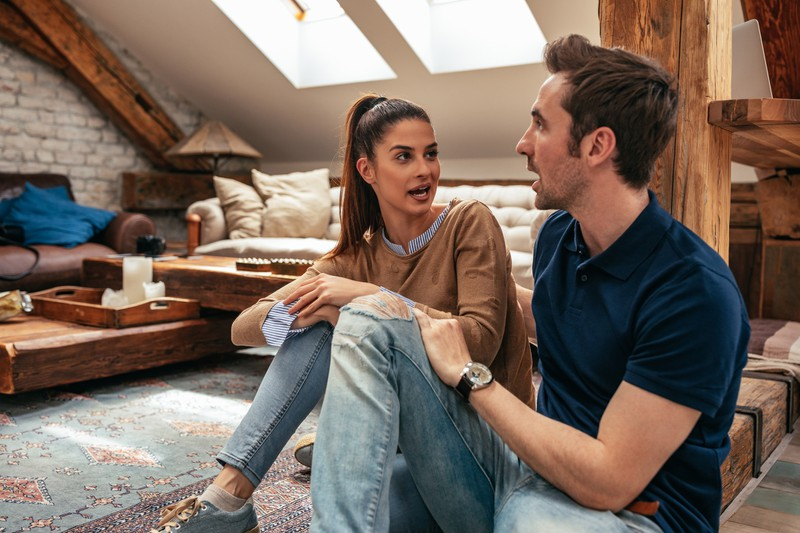 Paar unterhält sich im Wohnzimmer