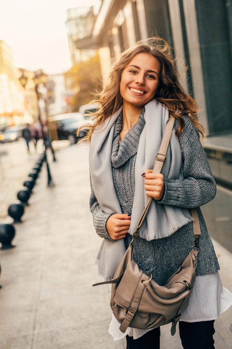 Frau mit langen, lockigen Haaren und Wollpullover strahlt