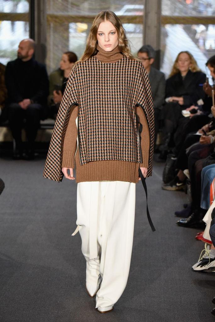 Frau mit weißer Hose und braunem Pullover