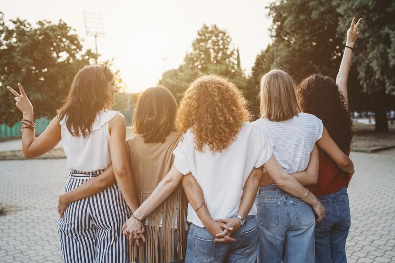 Frauen stehen Arm in Arm nebeneinander