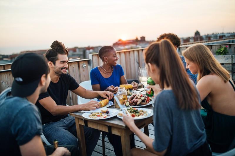 Freundesgruppe beim Abendessen auf dem Dach
