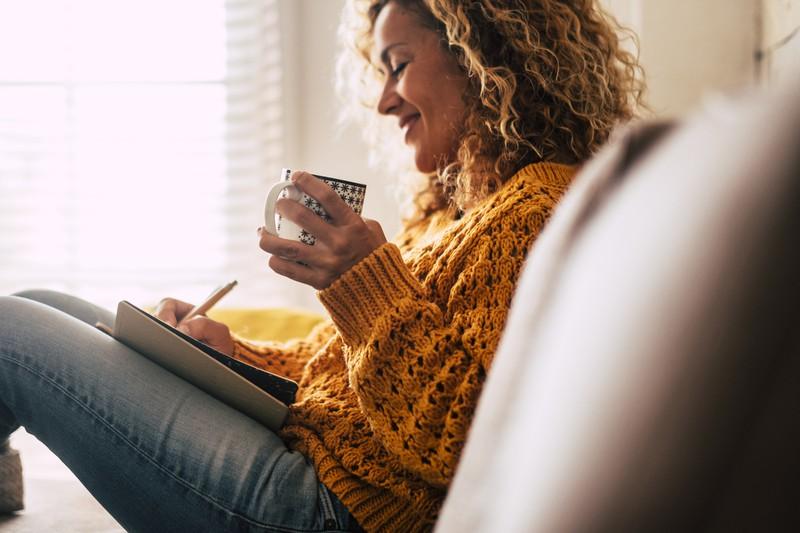 Lächelnde Frau schreibt Tagebuch