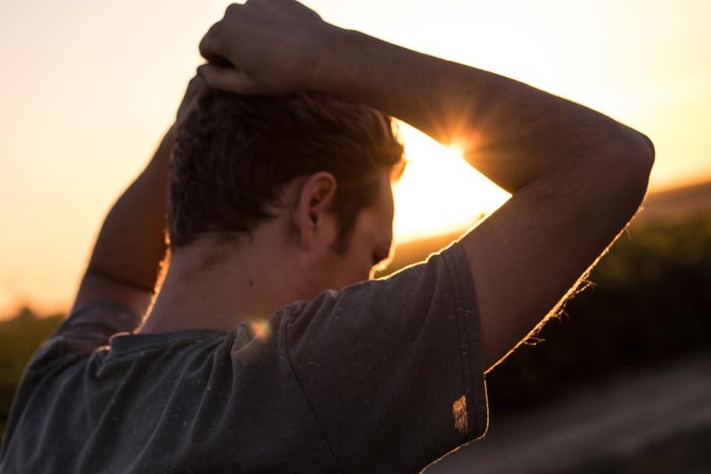 Ein Mann steht im Sonnenuntergang