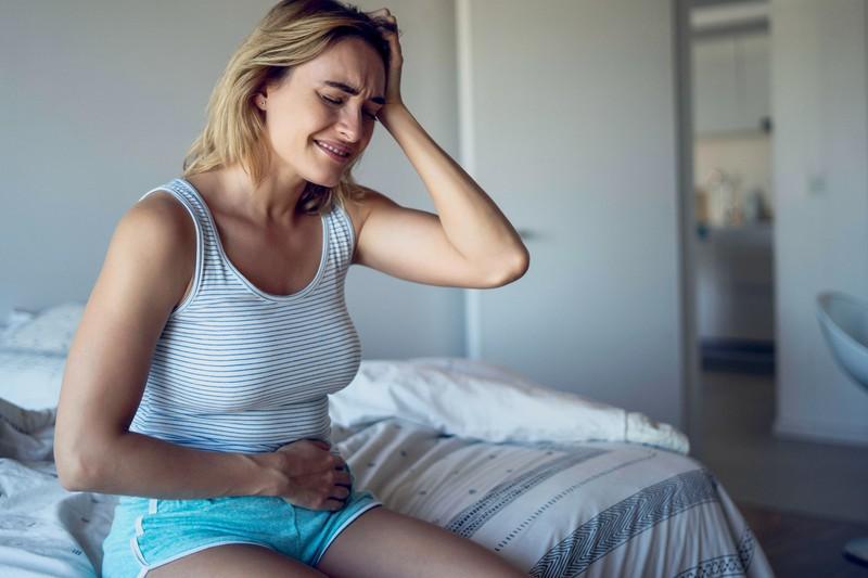 Frau fasst sich an ihren Bauch, weil sie vermutlich Schmerzen hat, die durch Eierstockkrebs verursacht werden