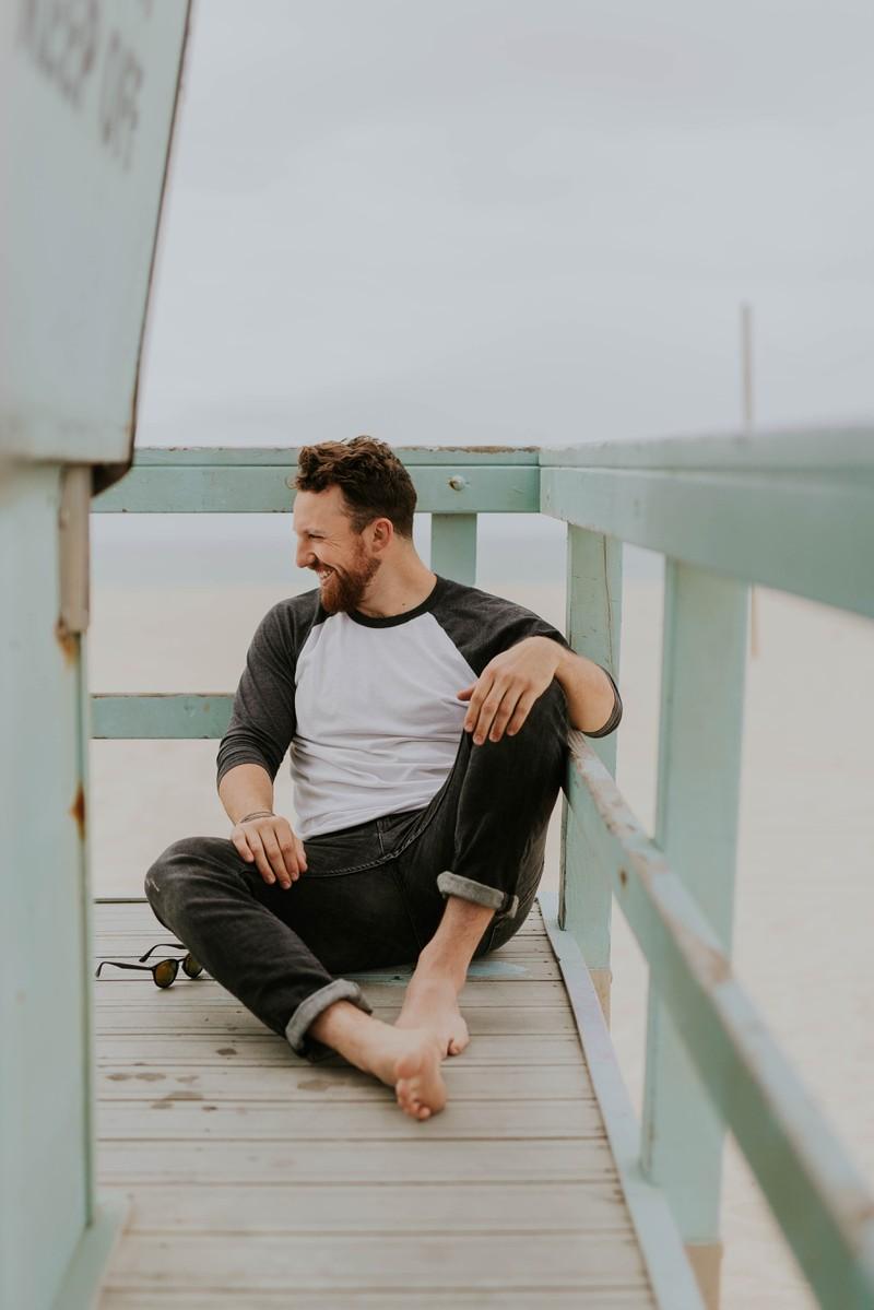 Ein Mann am Strand, der nicht daran denkt ihr zu antworten, weil er kein Interesse hat