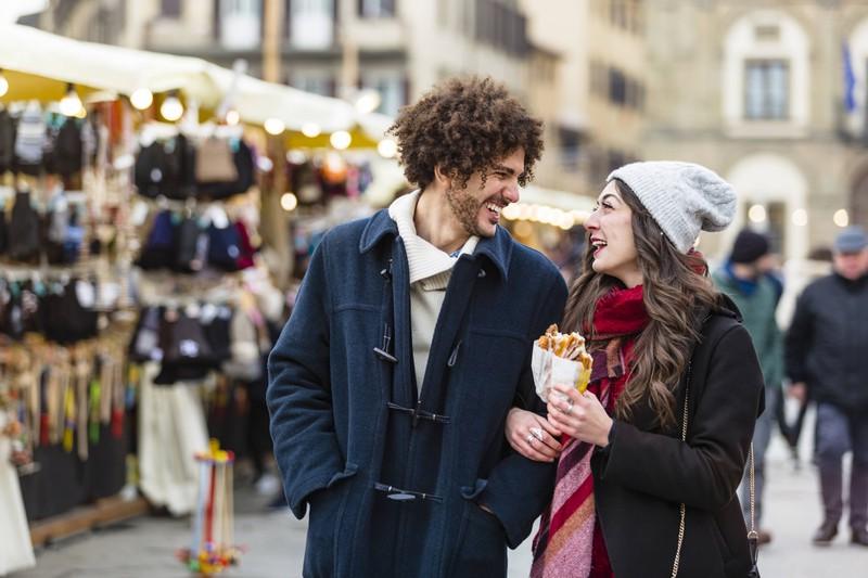 Glückliches Paar läuft über einen Weihnachtsmarkt und genießt dabei einen kalorienreichen Snack.