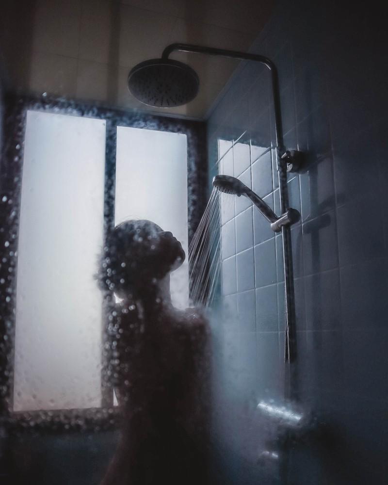 Frau, die gerade duscht und versucht, die Fehler zu vermeiden