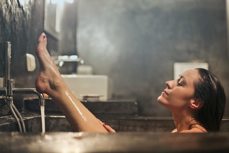 Frau, die gerade ein Bad nimmt und auf Dusch-Fehler verzichtet.