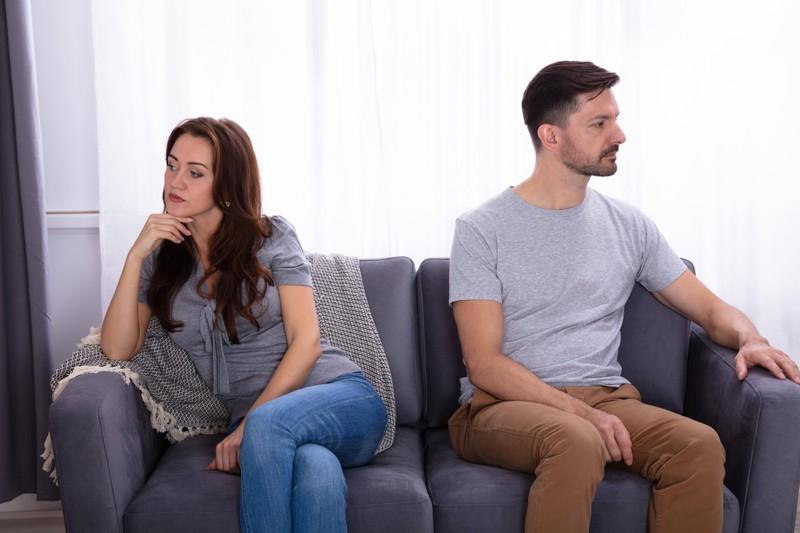 Ein Paar sitzt beleidigt auf dem Sofa und schaut voneinander weg. Sie will mit ihm Schluss machen