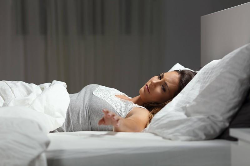 Eine Frau liegt alleine im Bett, nachdem sie ihrem Mann den Laufpass gegeben hat.