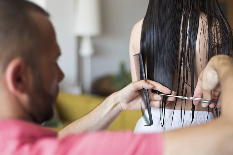 Wenn man sich selber die Haare schneidet, klemmt man sie wie auf dem Bild zwischen Zeige- und Mittelfinger ein.