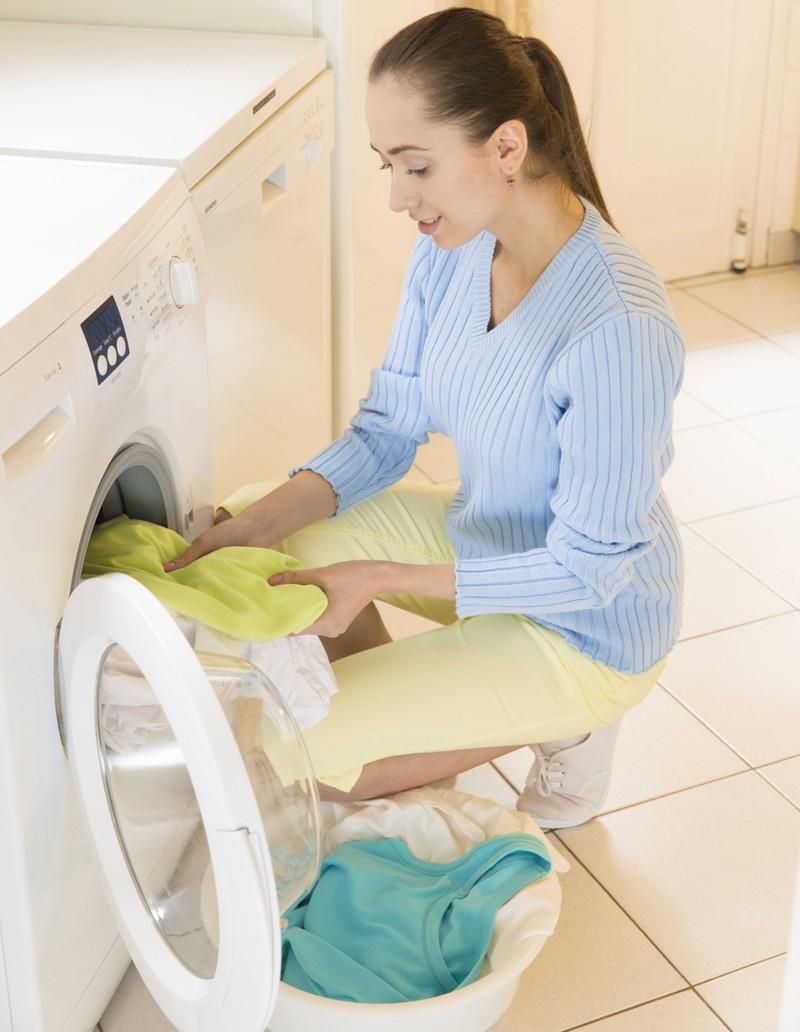Eine Frau nimmt saubere Wäsche aus der Waschmaschine