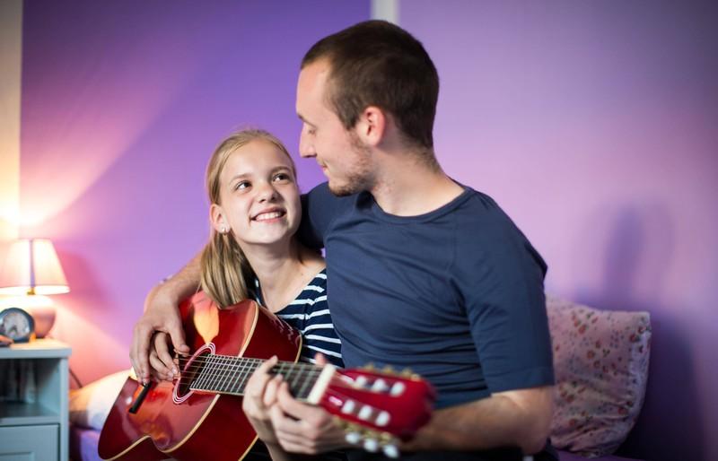Ein Vater zeigt seiner Tochter, wie man auf der Gitarre spielt