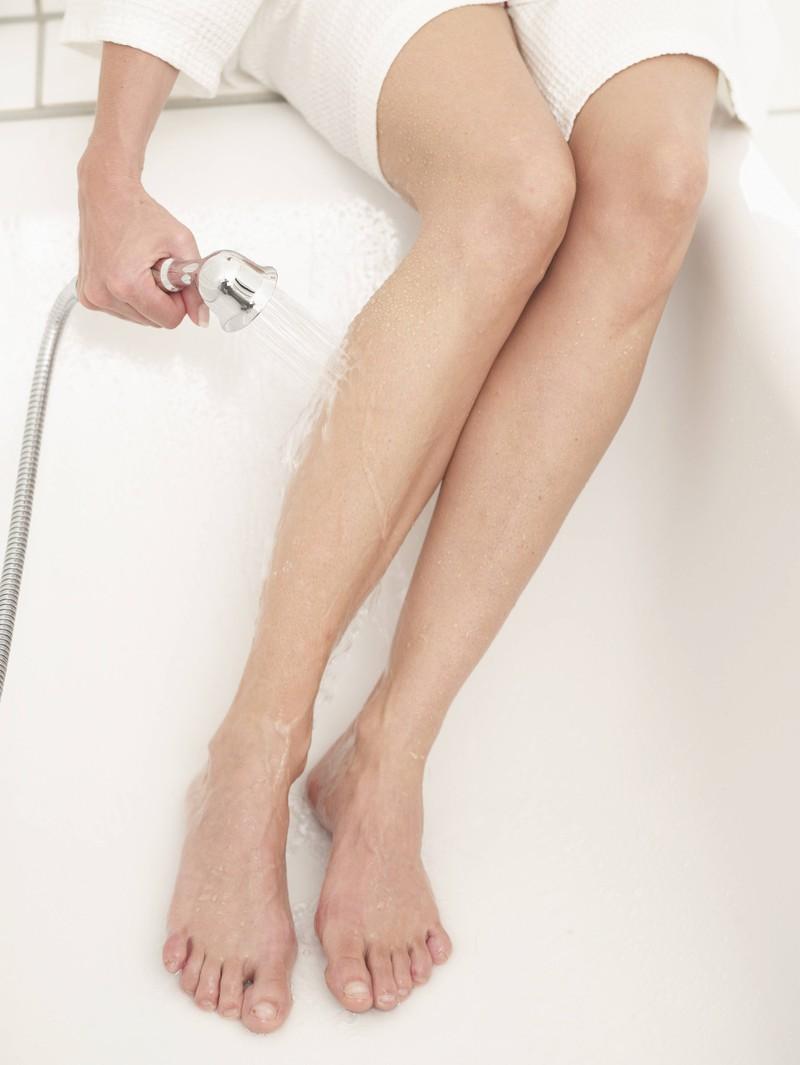 Eine Frau, die sich rasieren will und den richtigen Zeitpunkt in der Dusche abwartet, damit keine Rasierpickel auftreten
