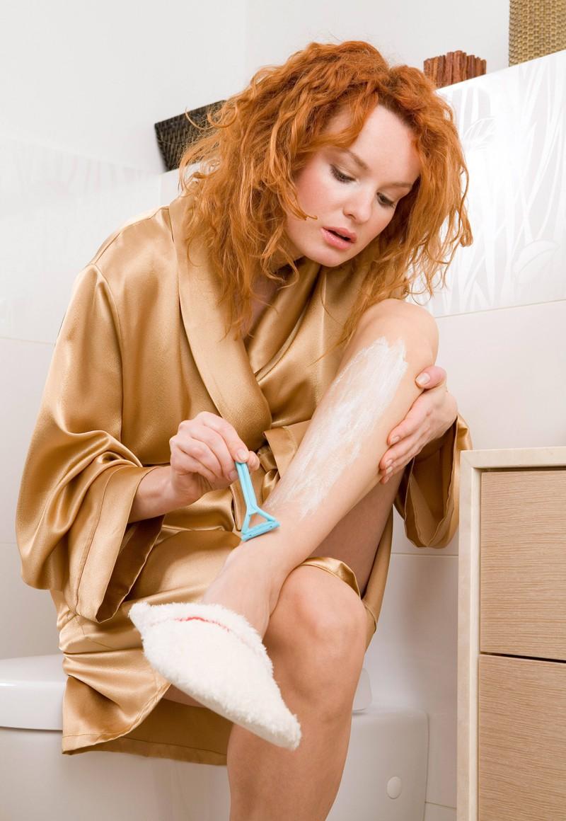 Eine Frau, die sich rasiert und vielleicht danach mit lästigen Rasierpickeln zu tun hat und wissen möchte, wie man sie nicht mehr bekommt
