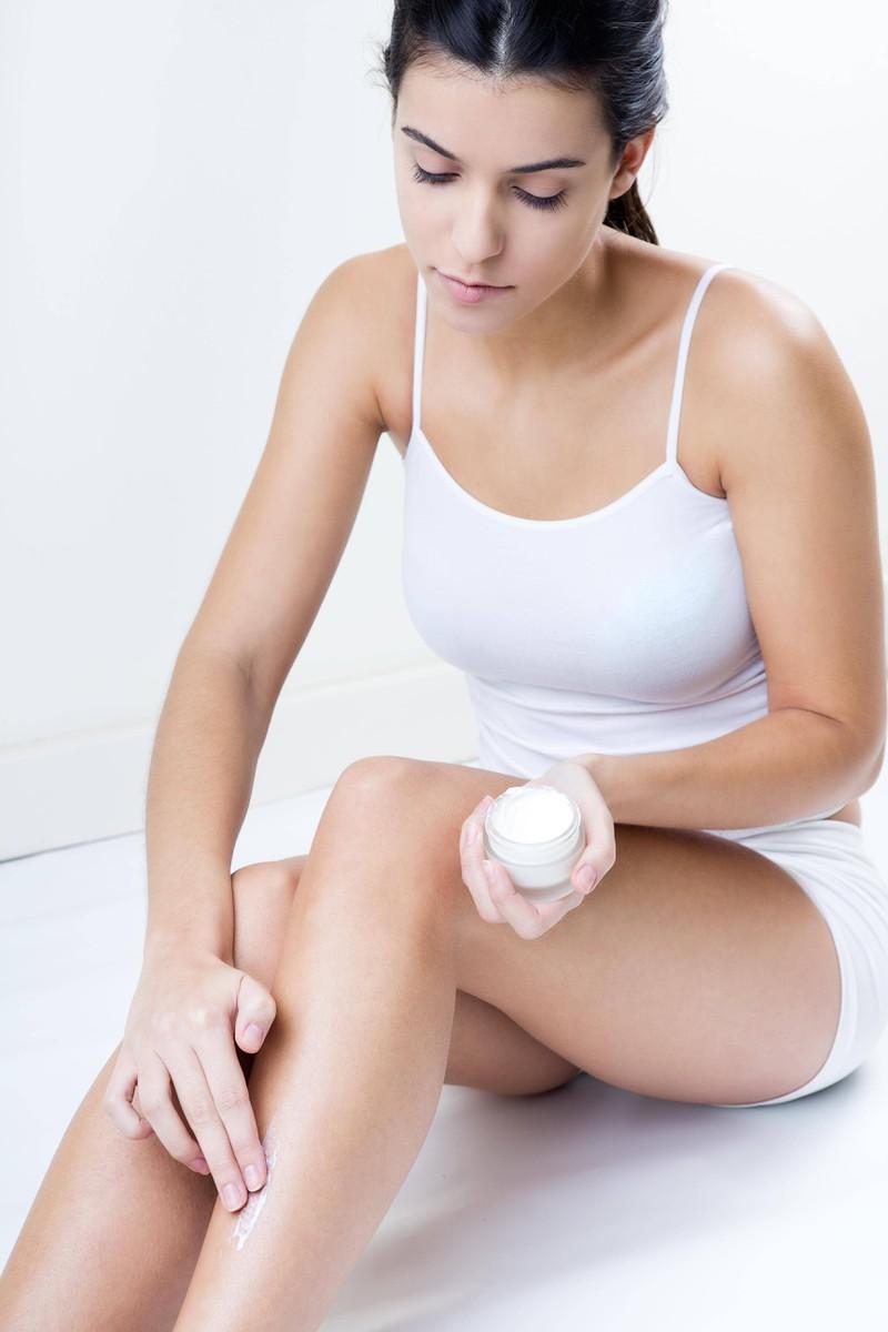 Es ist eine Frau zu sehen, die sich nach der Rasur eincremt, damit sie keine Rasierpickel bekommt