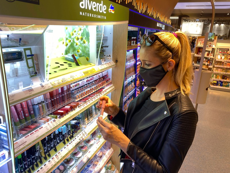 Die Frau sucht geeignetes Make-up, um sich trotz Maske gut zu schminken.