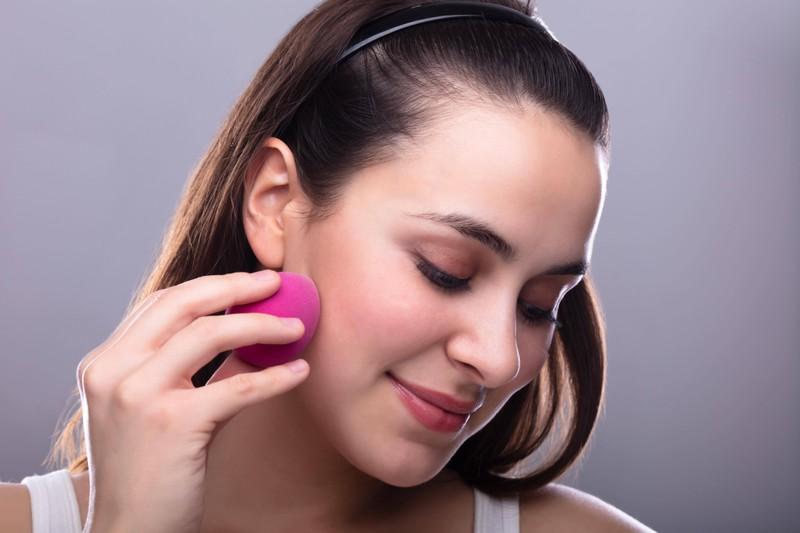 Trotz Maske erreicht die Frau durch einen Beauty-Blender eine leichte Deckkraft und sieht geschminkt aus.