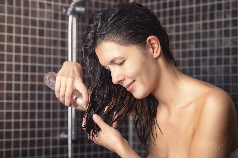 Das Bild zeigt eine Frau, die Pflanzenöl verwendet, damit ihre Haare im Sommer geschützt sind