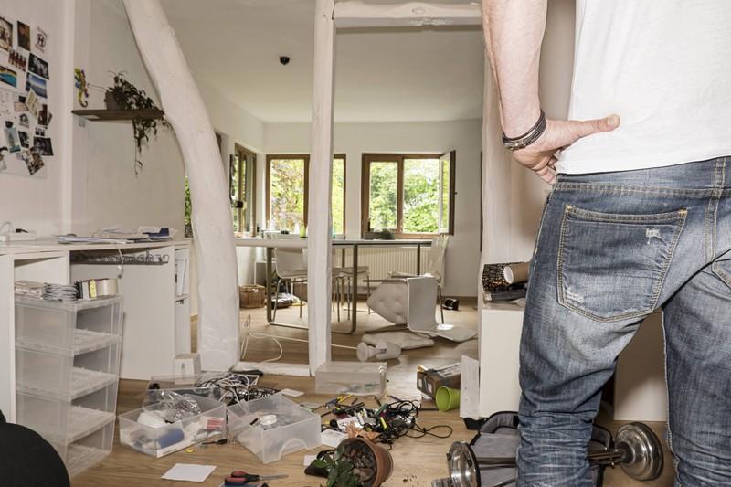 Ein Mann wohnt in einer unordentlichen Wohnung
