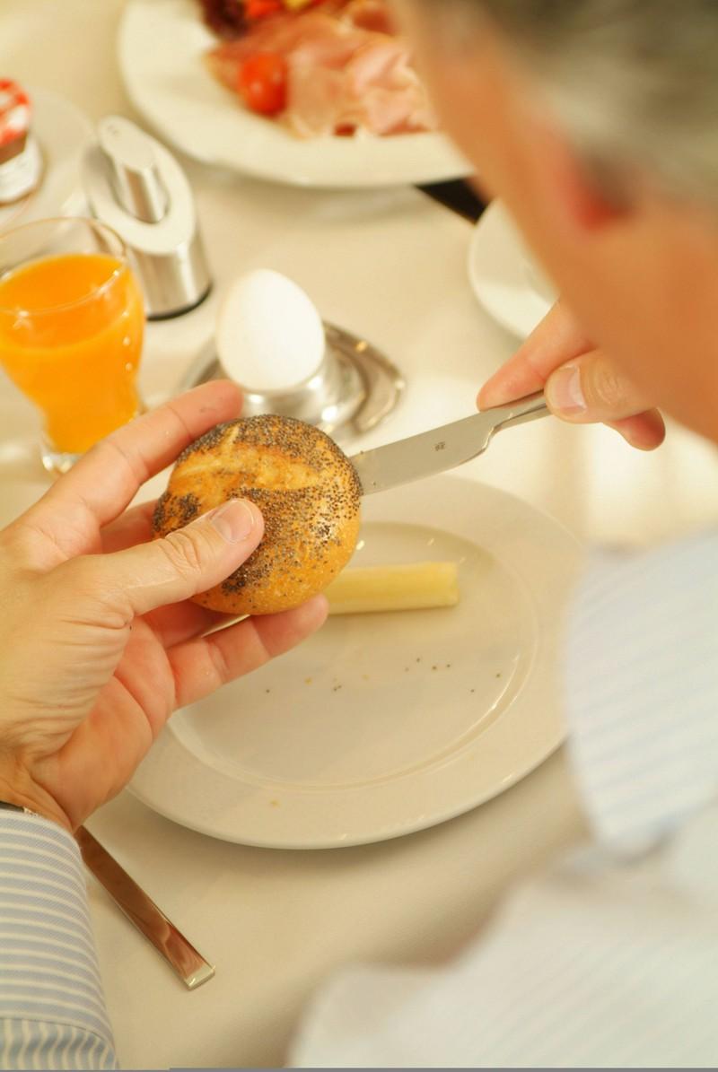 Mann beim Aufschneiden seines Brötchens am Frühstückstisch